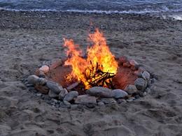 Détente autour d'un feu de camp sur la plage