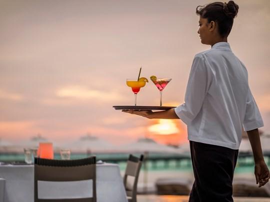 Sirotez des délicieux cocktails au coucher du soleil