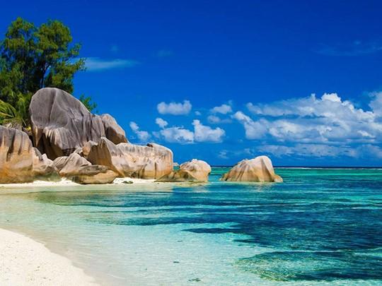 L'emblématique plage d'Anse Lazio dévoile son sable blanc parsemé de roches granitiques au bord d'une eau turquoise