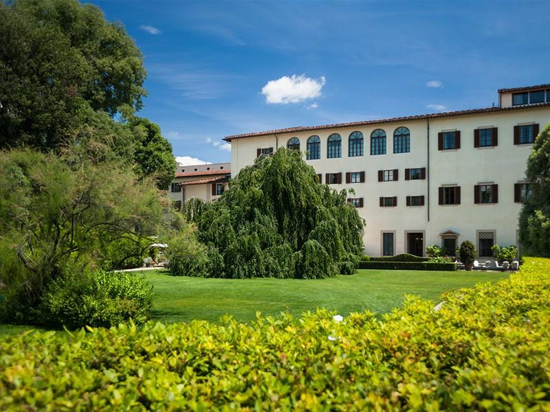 Vue de l'hôtel entouré de son jardin verdoyant