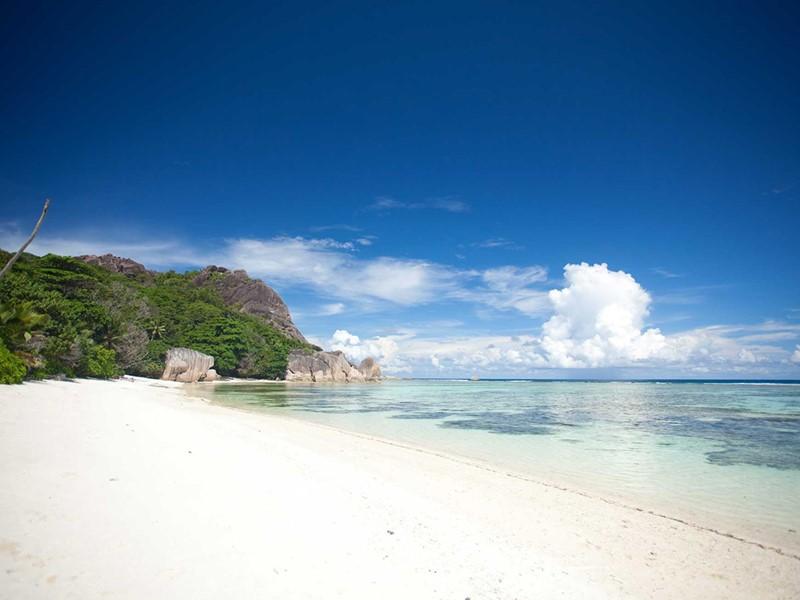 La plage de sable fin à l'eau turquoise de la Digue Island Lodge